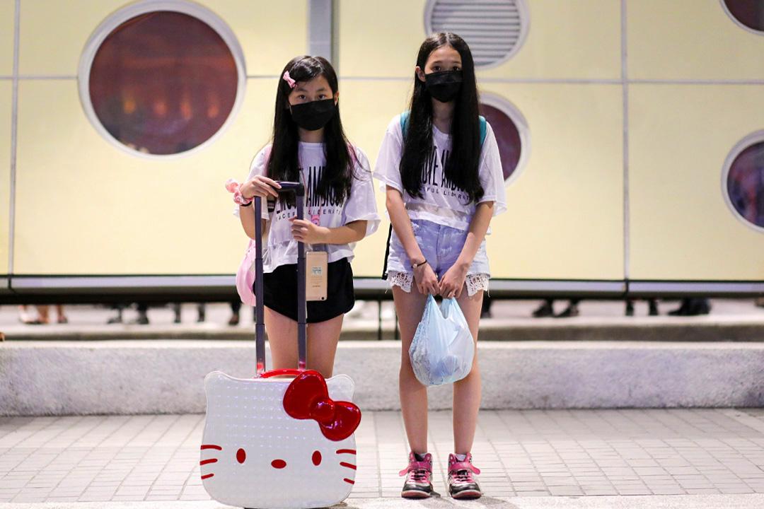 兩個近140公分高的小女生,拖着一個HelloKitty大頭造型的行李箱,準備接受訪問。