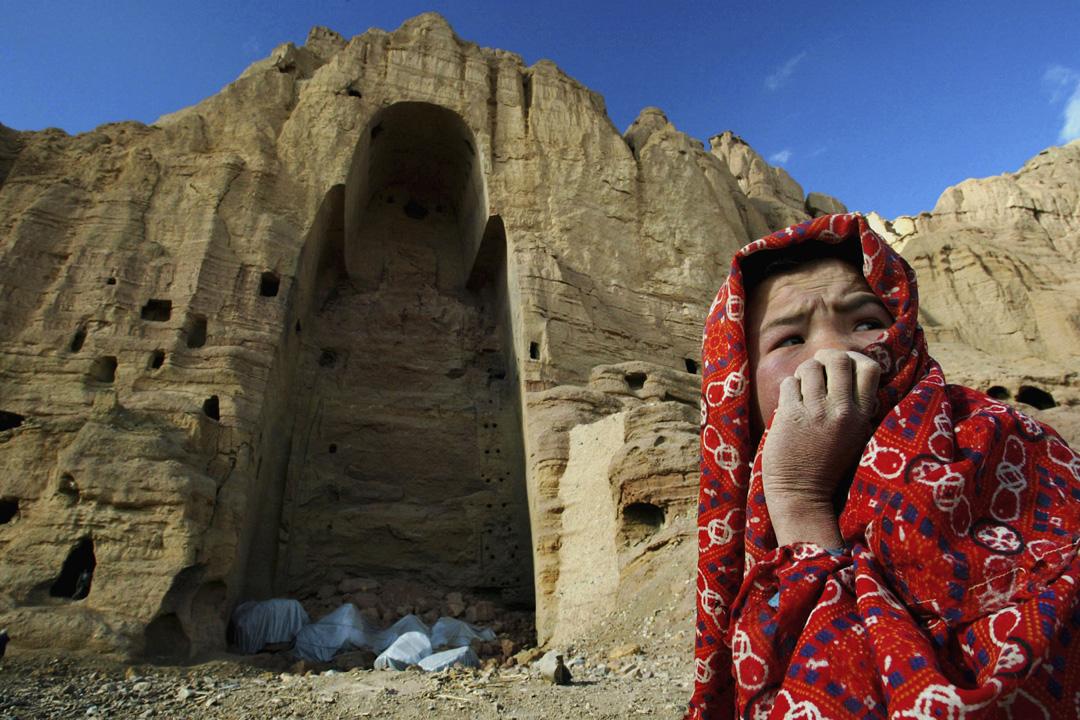 一名住在巴米揚洞窟的阿富汗女孩坐在巴米揚大佛的廢墟前。巴米揚大佛於2001年被塔利班炸毀。