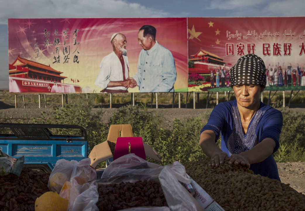 新疆,維吾爾族婦女在一幅宣傳共產黨思想的標語前販賣葡萄乾。
