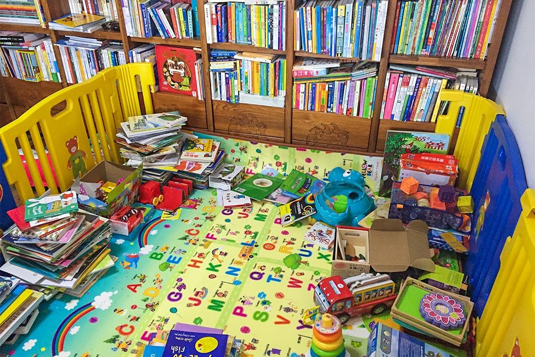 劉曉宇家中,半個客廳被規劃為孩子玩耍的區域,安置了半米高的彩色圍欄、柔軟防滑的地墊和一面書架。