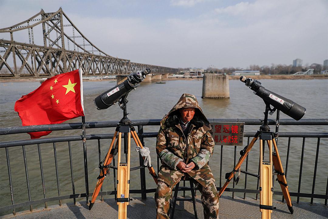 2017年4月1日,中國遼寧省丹東,一名男子坐在遊客區的望遠鏡旁。遊客可用望遠鏡觀看北韓。