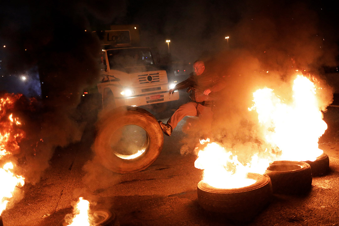 2017年4月28日,巴西聖保羅,一名警察在杜特拉公路上清除燃燒中的輪胎路障。當地示威者以輪胎作路障,抗議總統米歇爾·特梅爾提出的巴西社會保障制度改革建議。