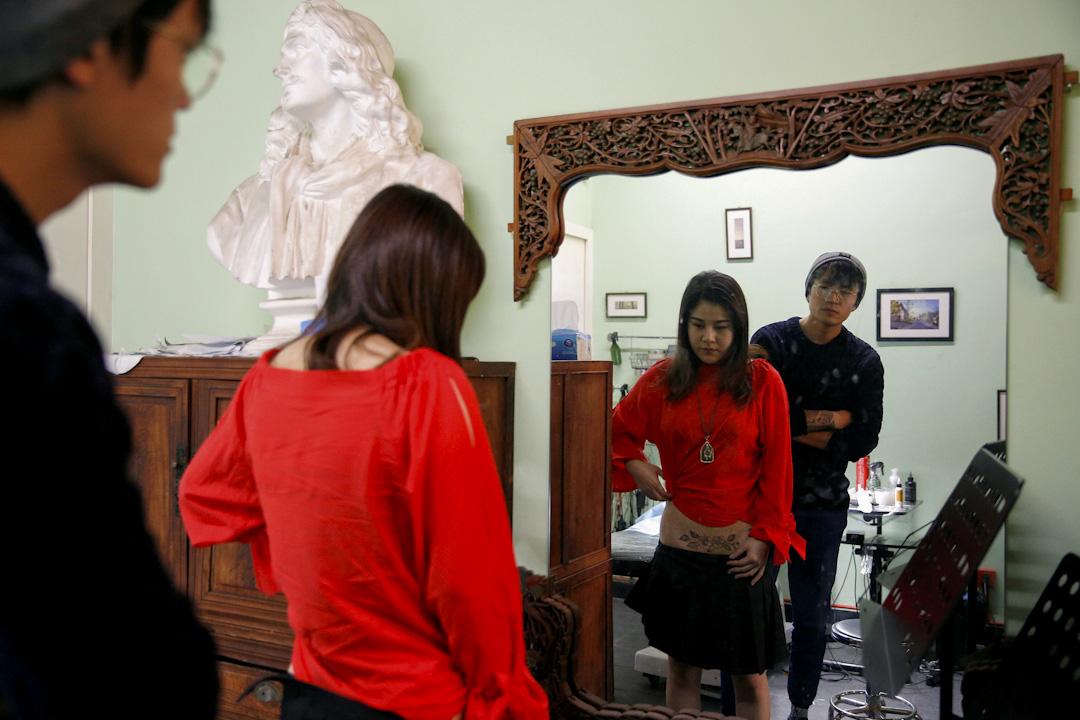 Kiki在鏡子前看自己的紋身。