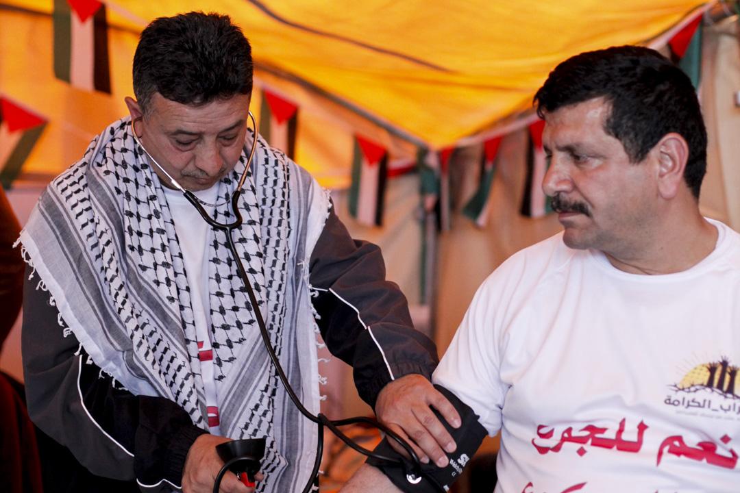 Ghassan Hamdan醫師為一起絕食的夥伴Bassam Nacm教授量血壓。
