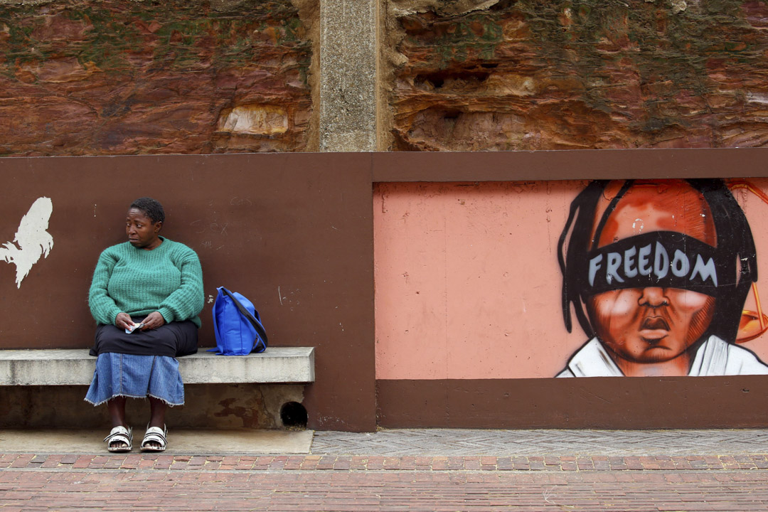2017年5月15日,在南非約翰內斯堡,一名婦人坐在寫有自由字眼的壁畫旁。反對黨派在憲法法院外示威,要求總統祖馬落台。