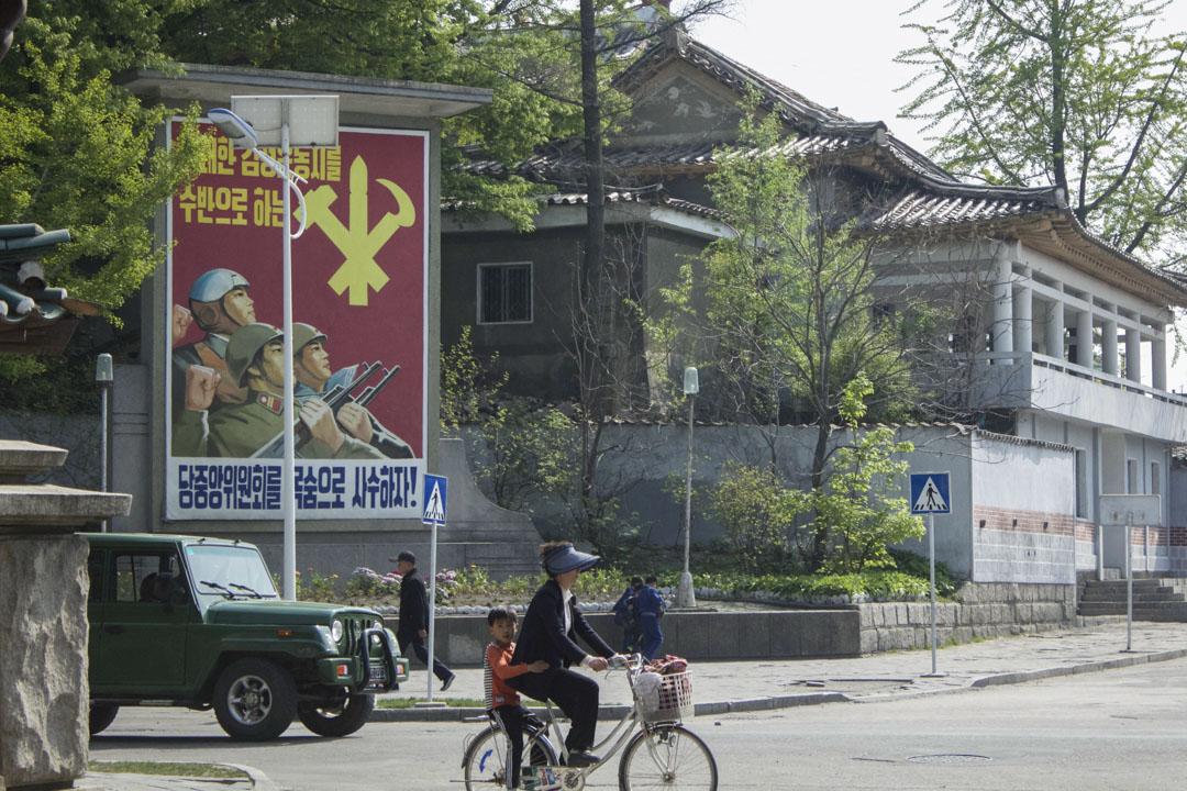 朝鲜旅行团所拍摄的当地街道,一位市民载著小孩踏单车。