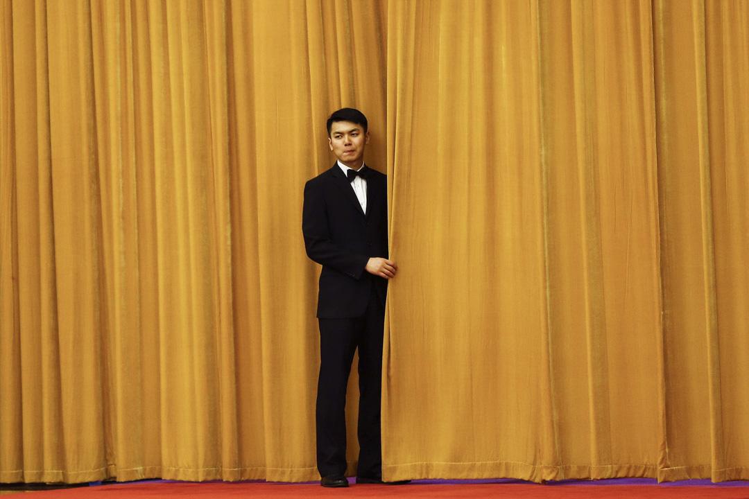 2017年5月16日,在北京人民大會堂,國家主席習近平正在「一帶一路高峰論壇」與多國元首會晤,一名工作人員將布簾拉上。