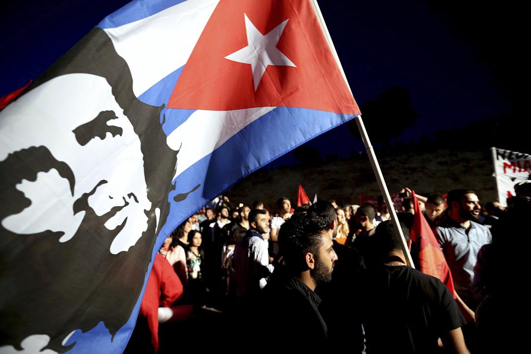 2017年5月1日,在塞浦路斯的首都尼科西亞舉行的五一勞動節抗議期間,一名示威者手持印有哲古華拉的古巴國旗。