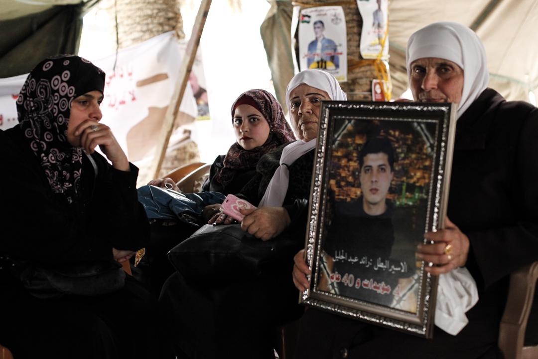 一名婦人與其餘囚犯家屬靜坐於帳篷內,手持參與絕食抗議的兒子照片。
