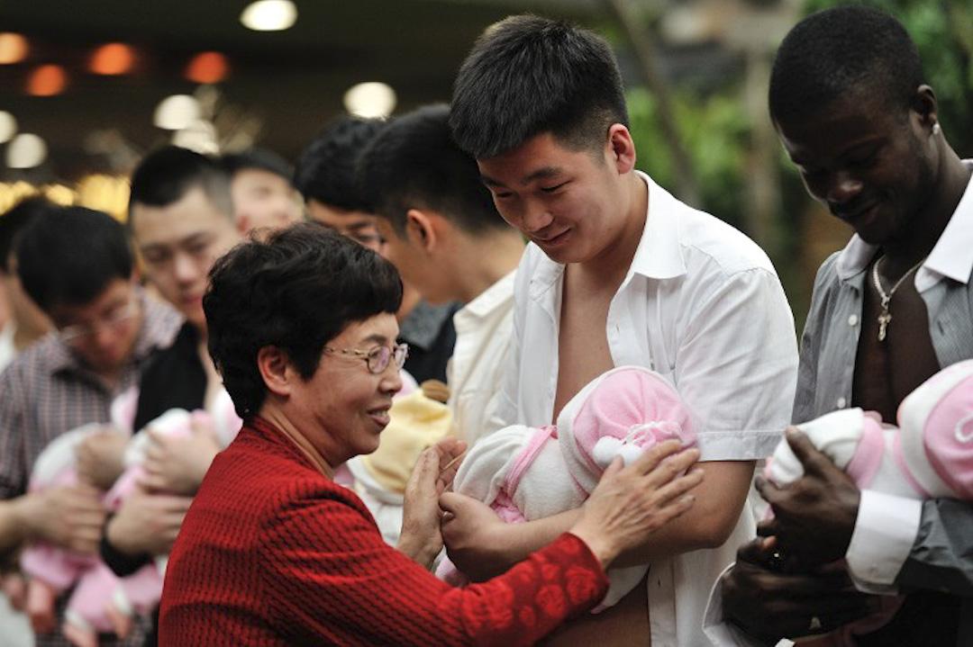 2016年5月8日,中國黑龍江省哈爾濱市一個慶祝母親節的活動,一眾男士手抱嬰兒玩具學習母乳喂養。