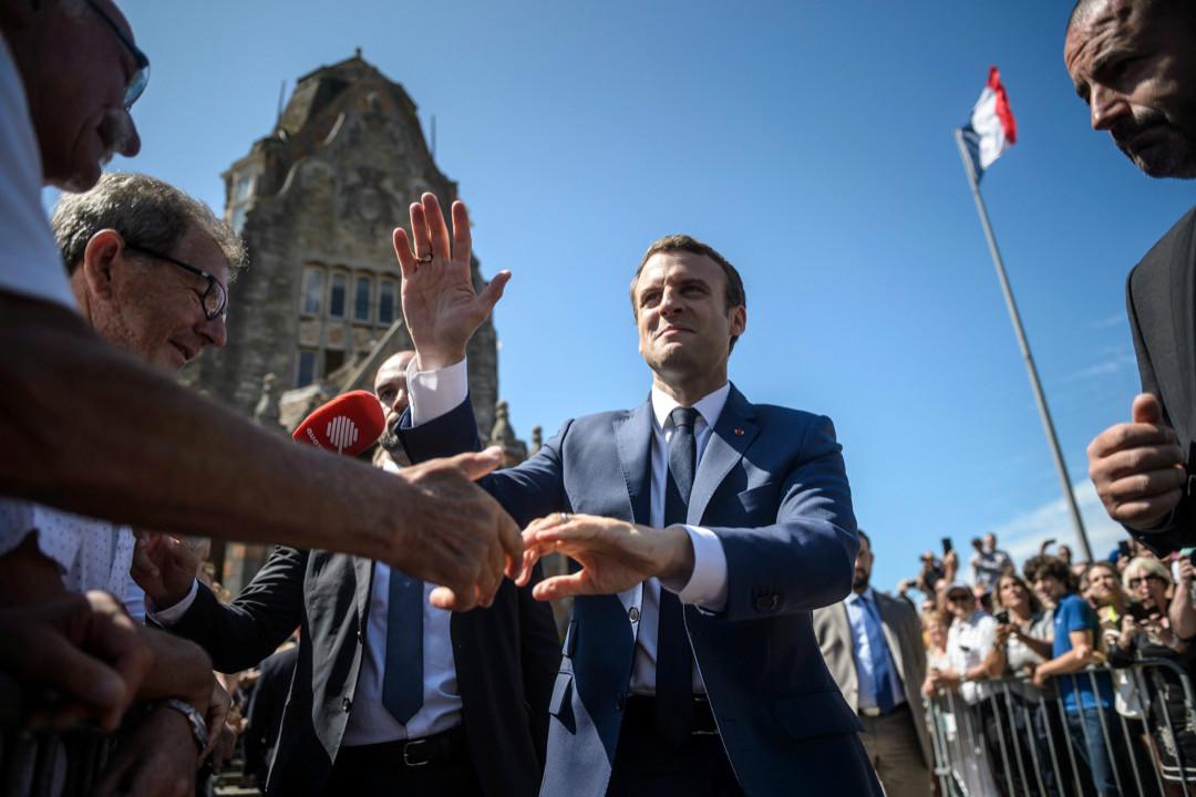 6月11日,在法國國民議會首輪投票中,馬克龍離開投票站時向支持者揮手致意。 攝:Christophe Petit Tesson/Reuters