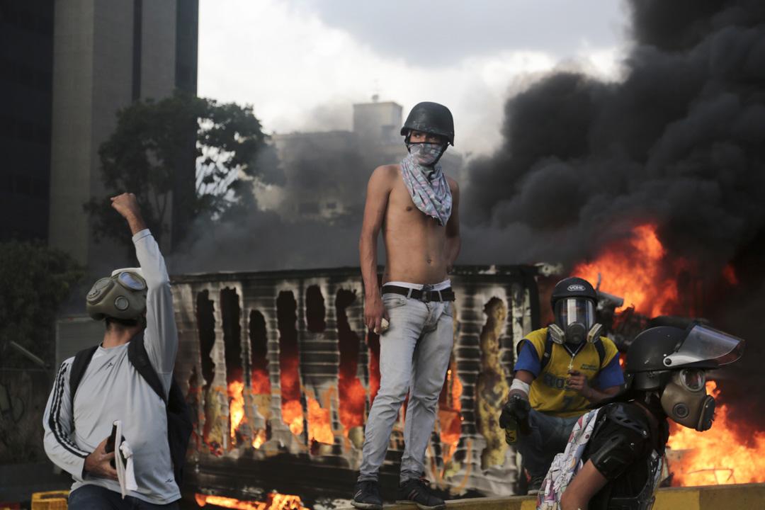 2017年5月27日,在委內瑞拉加拉加斯,反政府示威者在路障上嘗試監察著防暴警察的行蹤。後面的一輛被騎劫的貨車正被示威者焚燒起來。
