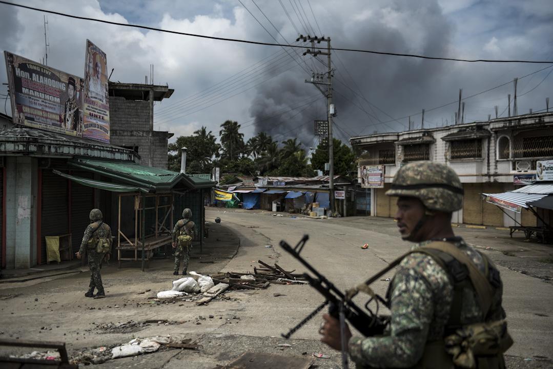 菲律賓軍警與自稱受「伊斯蘭國」感召的恐怖主義組織「密特集團」(Maute Group)在菲南馬拉威市(Marawi)正面交鋒,總統杜特地宣布棉蘭老島進入戒嚴狀態,交由軍隊負責平定當地「叛亂行為」。衝突至今尚未平息,圖為2017年6月6日,菲律賓軍警在市中巡邏。 攝:Jes Aznar/Getty Images