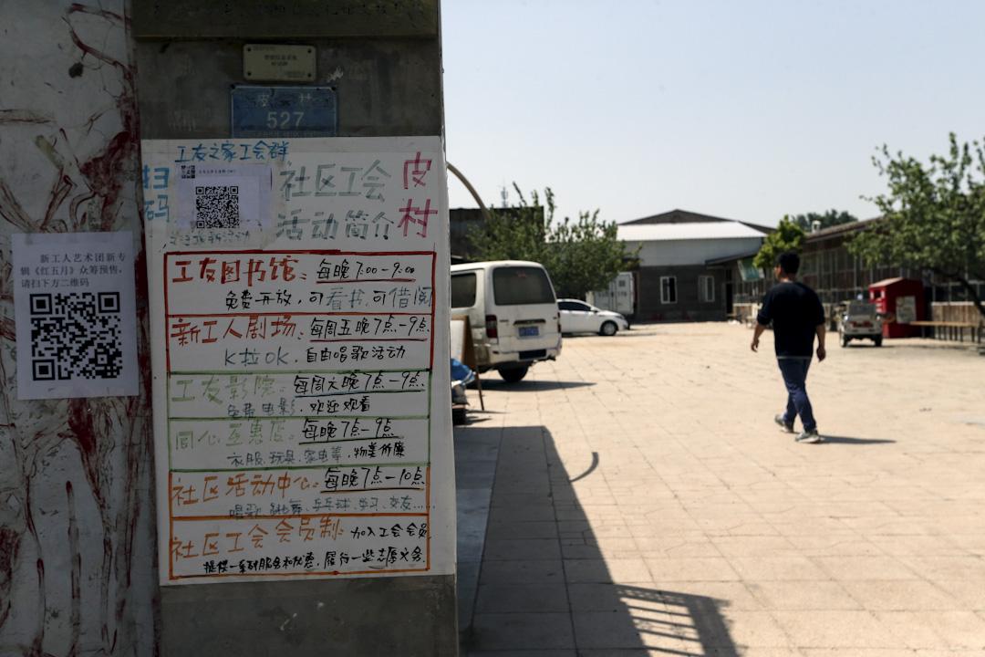 皮村社區文化活動中心的水泥門柱張貼著廣告體寫的圖書館、影院開放時間。