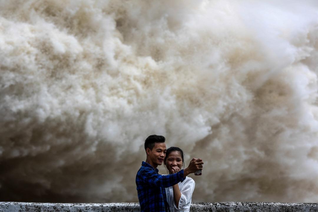 2017年7月20日,在越南和平省,一對情侶在和平水力發電廠排洪時合照。