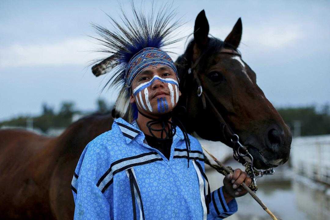 2017年7月11日,在加拿大卡加利,騎師Tyler Leather在卡城牛仔節中的原住民接力賽後與自己的戰駒合影。 攝:Todd Korol/Reuters