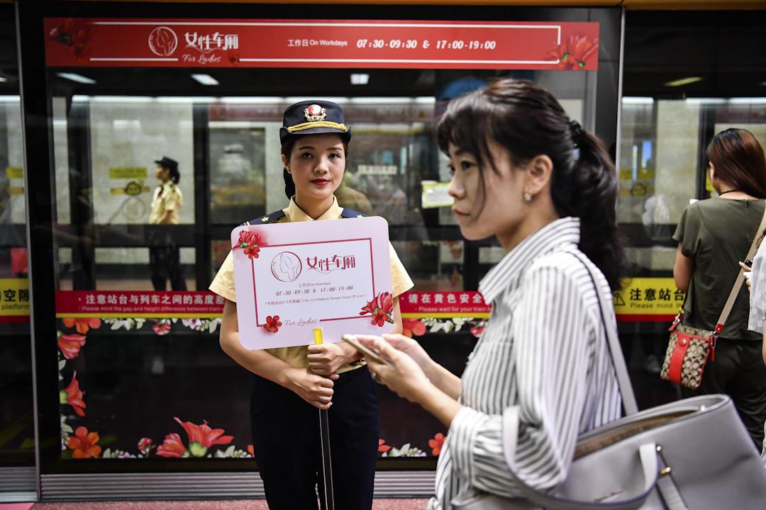 2017年6月28日,廣州地鐵1號線女性車廂啟用,現場地鐵志願者舉牌指引乘客。   攝:鍾振彬 / Imagine China