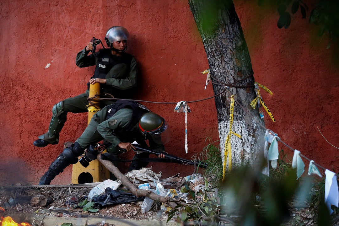 2017年7月26日,在委內瑞拉加拉加斯,防暴警察試圖越過反政府示威者築成的路障。