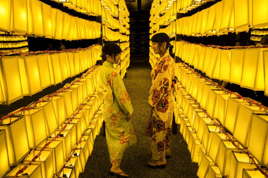 2017年7月13日,日本全國舉行御靈祭,悼念二戰中失去性命的亡魂,兩名穿著和服的女子在掛滿黃色燈籠的靖國神社裡遊走。