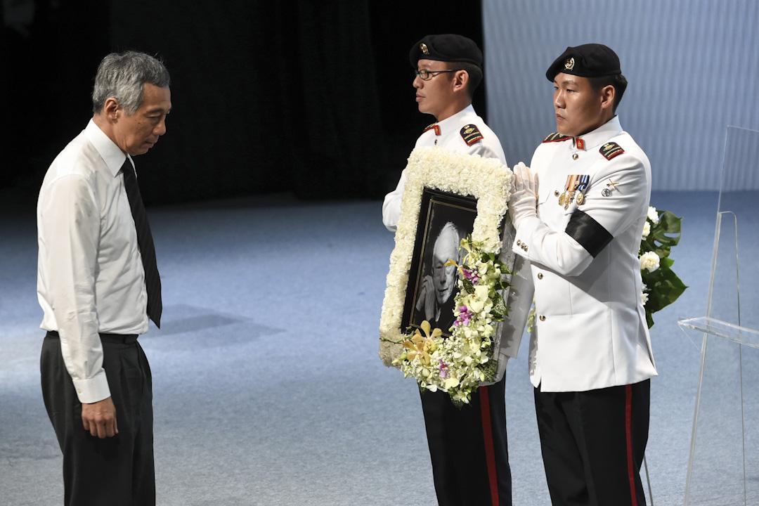 李光耀的子女為了父親故居的保留和拆除,而衍生的一場公開糾紛,揭露了新加坡政治制度雖然在控制民眾和一般官員方面,有相當大的作用,不過面對高層政治領導,卻顯得無能為力甚至縱容,對後李光耀時代的新加坡和行動黨而言,是一個相當嚴重的問題。圖為李光耀於2016年逝世,其兒子及總理李顯龍而向其遺照。 攝:Roslan Rahman /AFP/Getty Images