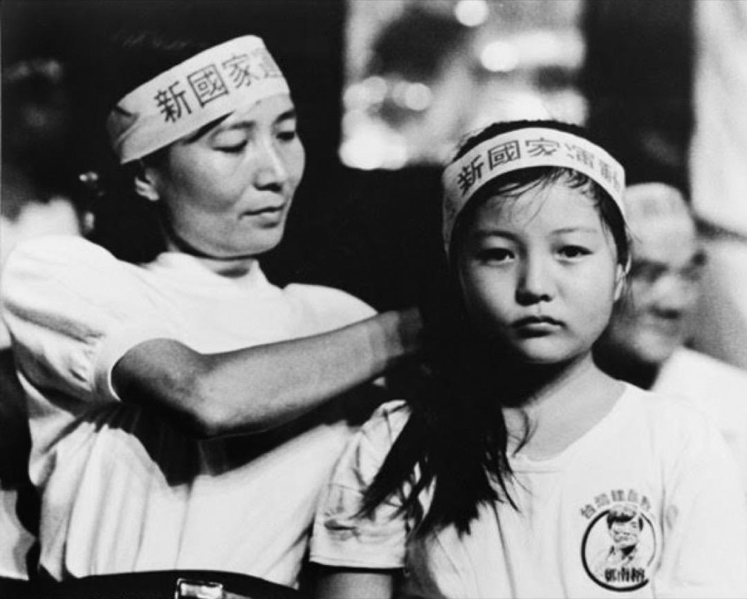 鄭南榕於1989年4月7日自焚身亡後,他的遺孀葉菊蘭於同年底宣佈參選立法委員,訴求「請你陪我打一場母親的戰爭」,葉菊蘭從此踏入台灣政壇。圖為葉菊蘭在街頭替時年9歲的女兒鄭竹梅整理頭髮、繫上頭巾。
