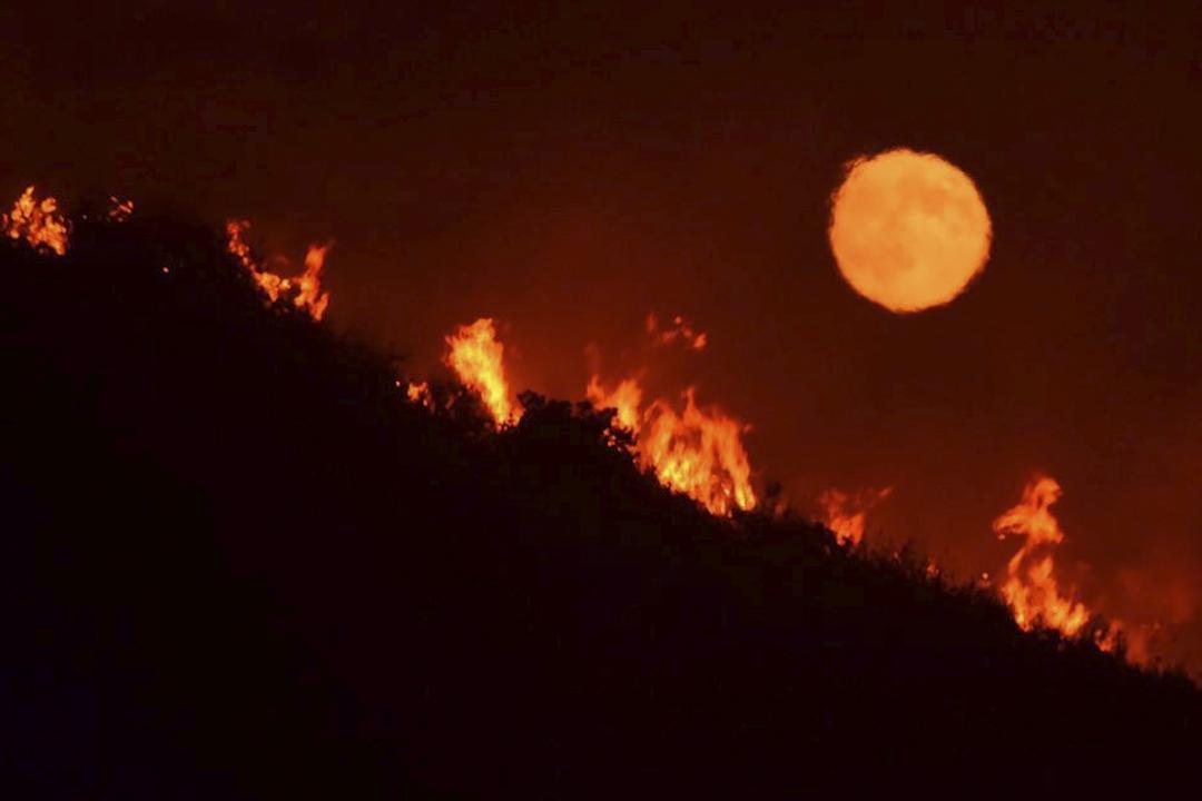 2017年7月7日,美國加州聖瑪利亞附近的66號公路旁發生山火,火焰燃燒的同時,一輪滿月正好升起。