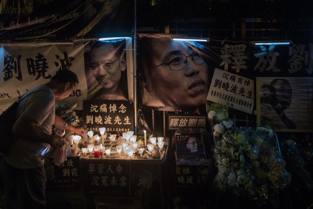 遊行人士到達中聯辦後,放下鮮花和蠟燭後離開。