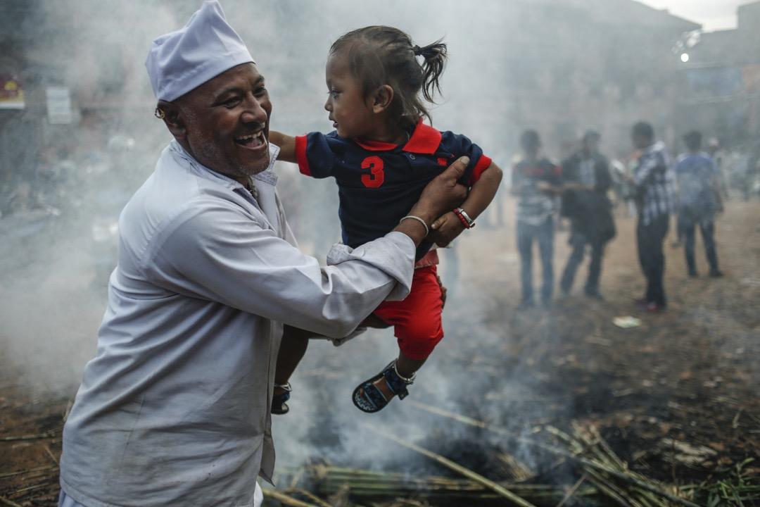 2017年7月21日,在尼泊爾加德滿都,群眾在慶祝印度教節日 Gathemangal,焚燒神話中的惡魔 Ghanta Karna 的稻草人,一名男子抱著嬰兒圍著火堆走。