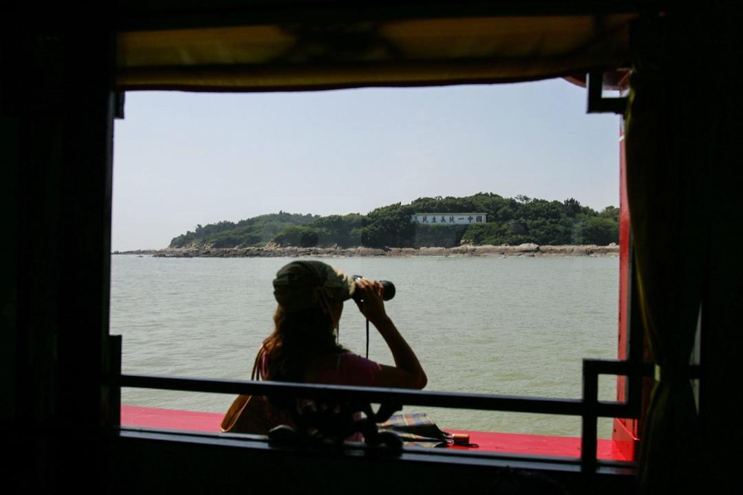 根據前總統李登輝的「兩國論」說法,台灣自1991年修憲以來,已將兩岸關係定位在國家與國家。圖為一名中國遊客在觀光船上透過望遠鏡遠觀對岸屬於台灣的金門島。