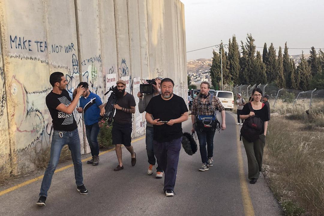 艾未未與攝製組在以巴邊界的隔離牆旁行走。