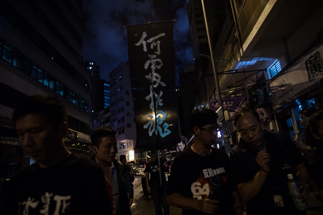 遊行隊伍前排舉起了一支旗幟,黑布上寫上「何處招魂」四字。