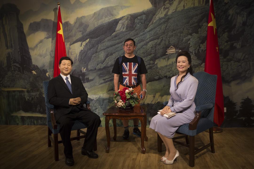 2017年7月1日,香港回歸20年之際,香港杜莎夫人蠟像館中,一位身穿印有英國國旗的T恤的市民和國家主席習近平及其夫人彭麗媛的蠟像合影。 攝:陳焯煇/端傳媒