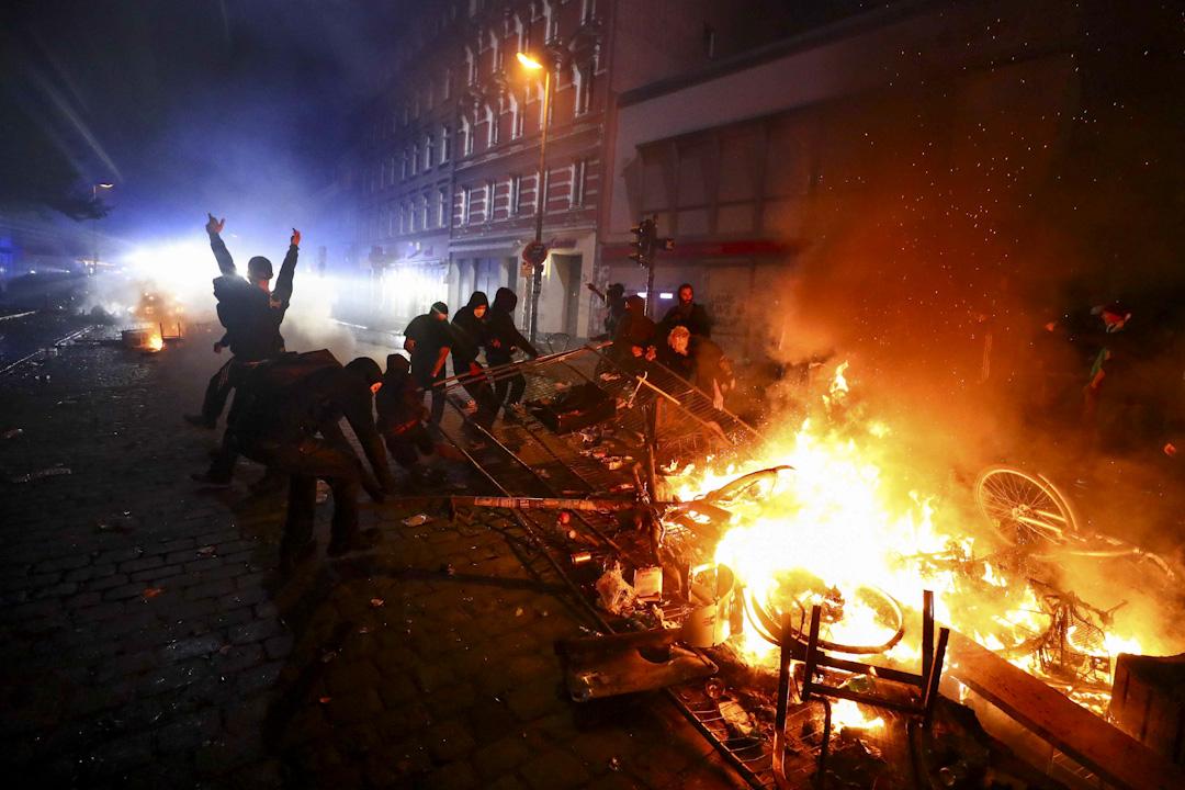 2017年7月7日,於漢堡市中心的反全球化遊行,約1.2萬名環保、工會、學生、社運和教會人士,當中約1000名穿著黑衫的極左示威者戴了頭套和面罩,他們的口號是:「歡迎來到地獄」。部份示威者於入夜後焚燒汽車。 攝:Pawel Kopczynski /Reuters