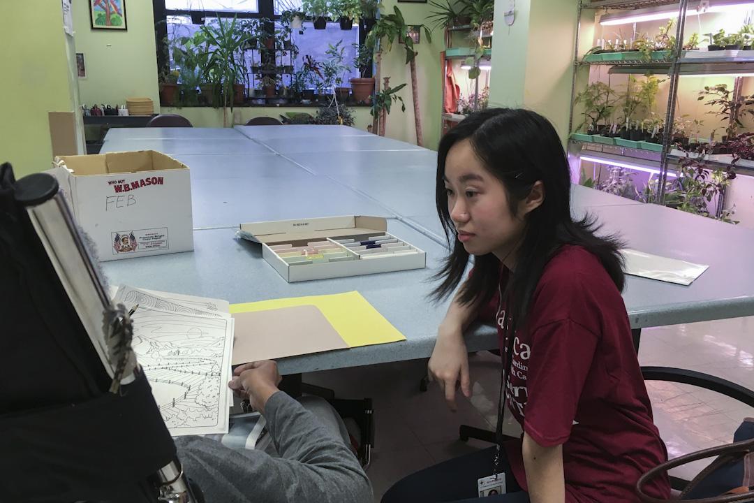 哥倫比亞大學的一位志願者,正在陪同一位居民下棋。