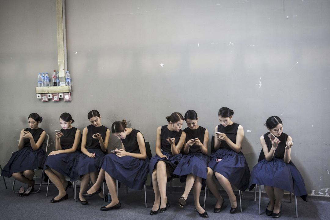 大陸微信公眾號發展蓬勃。這些或者稱為自媒體,面對的是數量上億的、嚴重依賴智能手機獲取資訊並且有較強消費慾望的年輕受眾。圖為廣州一個活動後台,一群年輕女生各自觀看手機。