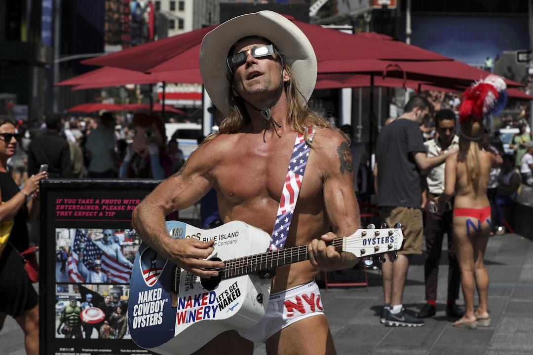 2017年8月21日,美國紐約時代廣場,一位只穿著底褲的吉他手戴著特製的日蝕眼鏡準備看日蝕。