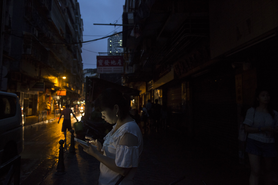 黃昏,電力依然未恢復,澳門依然漆黑一片,一名女子在街道上用手機。 攝:林振東/端傳媒