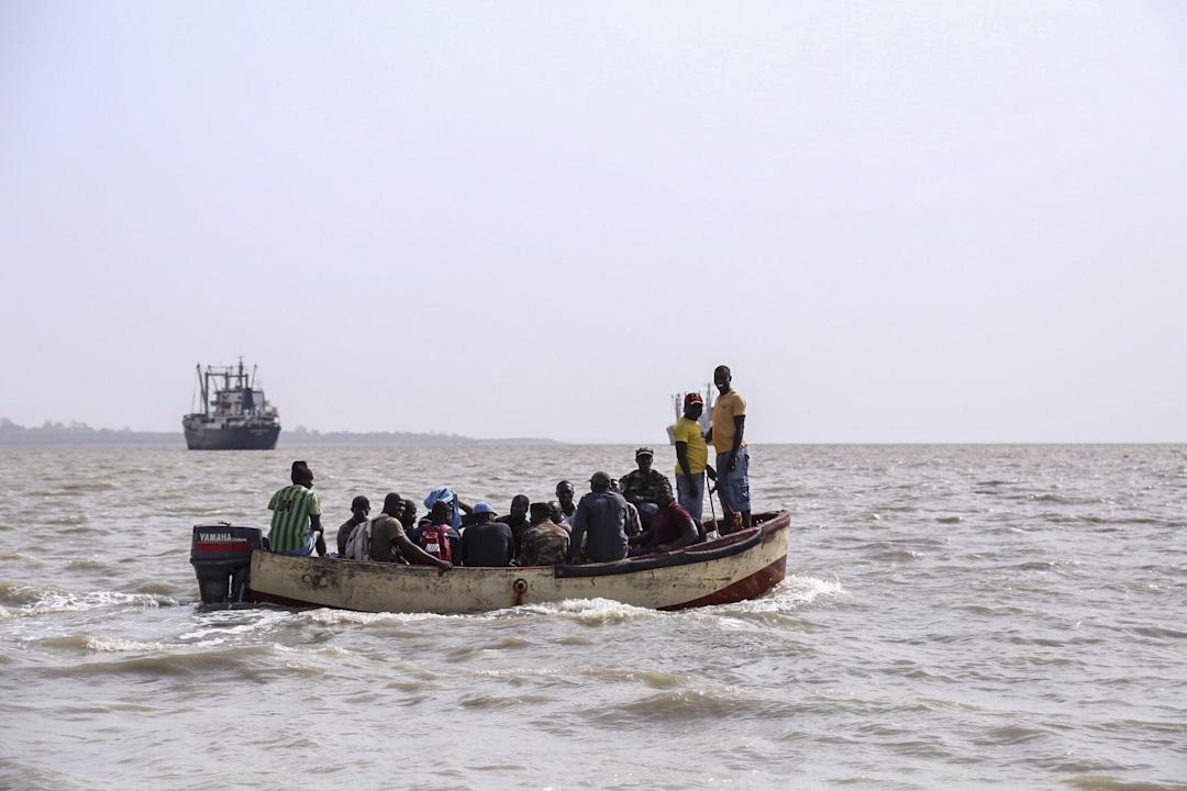 幾內亞比索港口外海,小舟正載著當地漁工前往中國漁船上工作。 攝:何欣潔/端傳媒