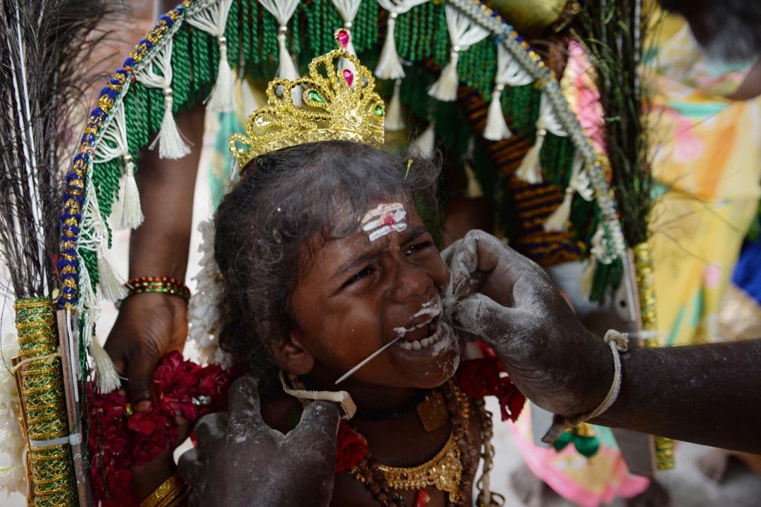 2017年8月13日,在印度清奈,一名印度教小信徒在進行傳統宗教儀式。旁人替她將鐵枝穿過其臉頰,過程表現出痛苦的神情。
