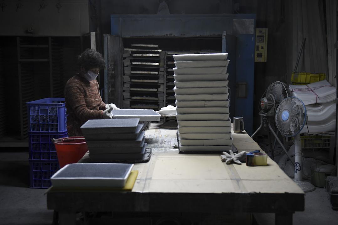 清輝窯依然是台灣唯一的陶瓷過濾網和陶芯製造商,並以陶瓷射出成型的技術持續開發各種精密元件,仰賴的是過去二十多年來緩慢累積的專業技術與量產設備。圖為工人正處理陶瓷過濾網。