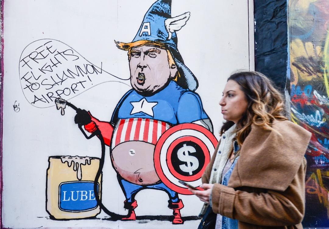 2017年3月15日,在愛爾蘭首都都柏林,一名途人行經一個塗鴉了特朗普穿上「美國隊長」制服的酒吧門口。