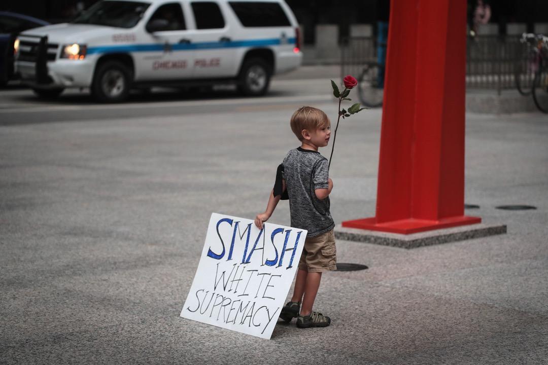 2017年8月13日,在美國芝加哥,一名小男孩手持標語,反對白人至上種族主義。弗吉尼亞州早前爆發白人種族主義衝突,造成3人死亡。