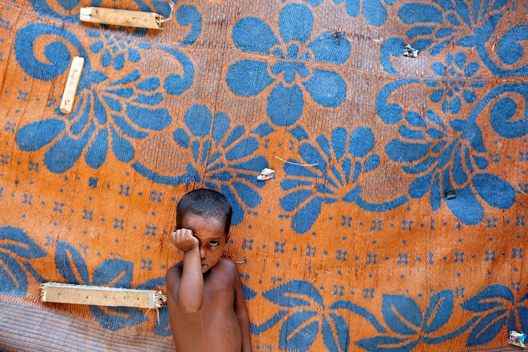 2017年8月17日,在印度德里,來自羅興亞族的小男孩站在簡陋的棚寮之外。 攝:Cathal McNaughton/Reuters