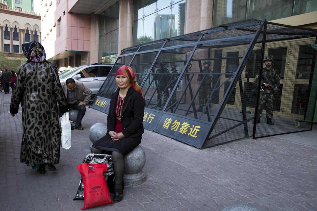 2014年5月1日,新疆烏魯木齊,武警持槍站崗執勤,一位維吾爾族婦女在保護籠外休息。 攝:Imagine China