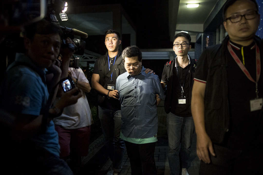 2017年8月15日,重案組探員將被捕的林子健由旺角警署,押送到位於馬鞍山錦豐苑錦萱閣的寓所進行搜屋調查。 攝:林振東/端傳媒