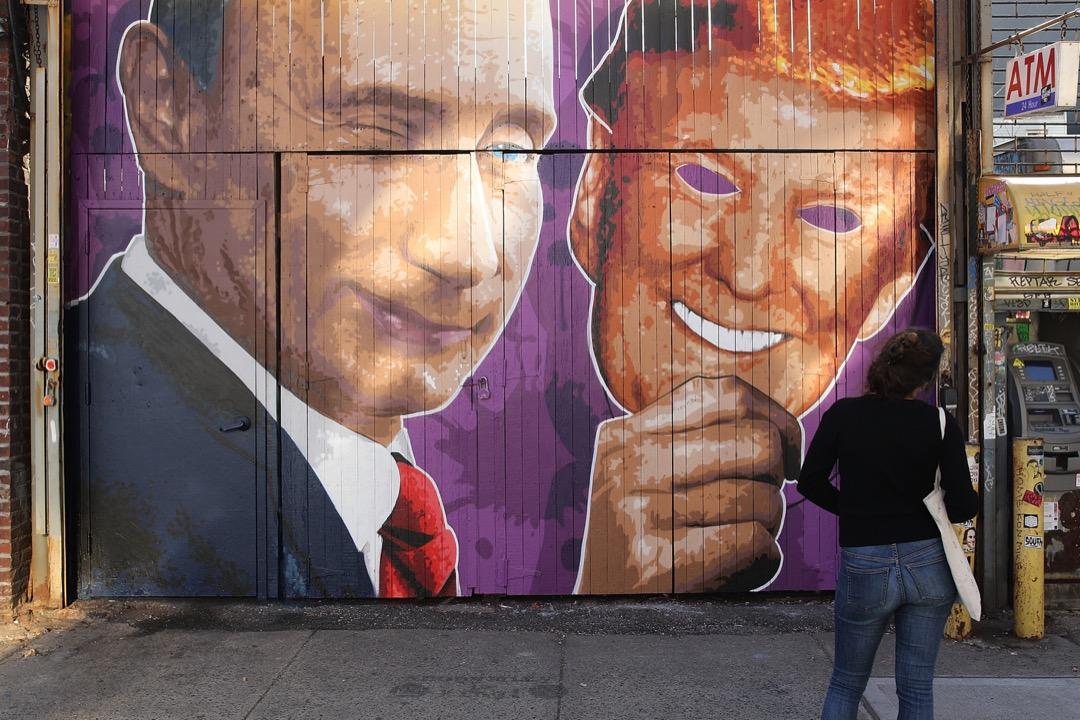 2017年2月25日,在美國紐約市布魯克林區,一名途人行經一個畫上了俄羅斯總統普京拿著特朗普面具的店鋪門口。
