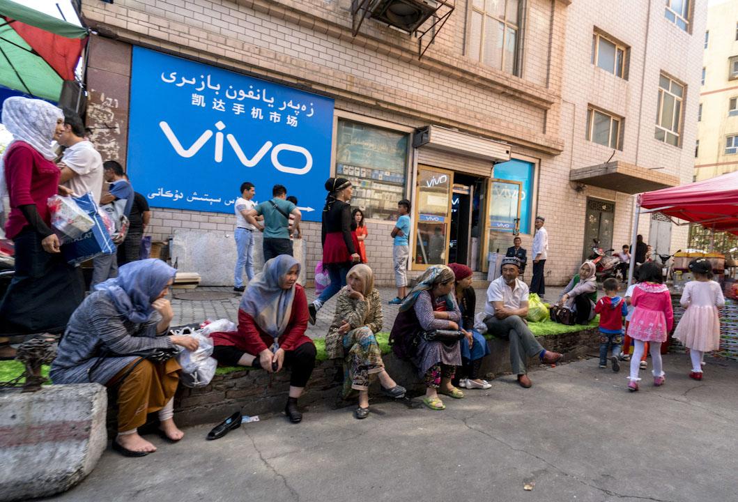 2016年6月18日,維吾爾族婦女購物後在手機市場前休息。