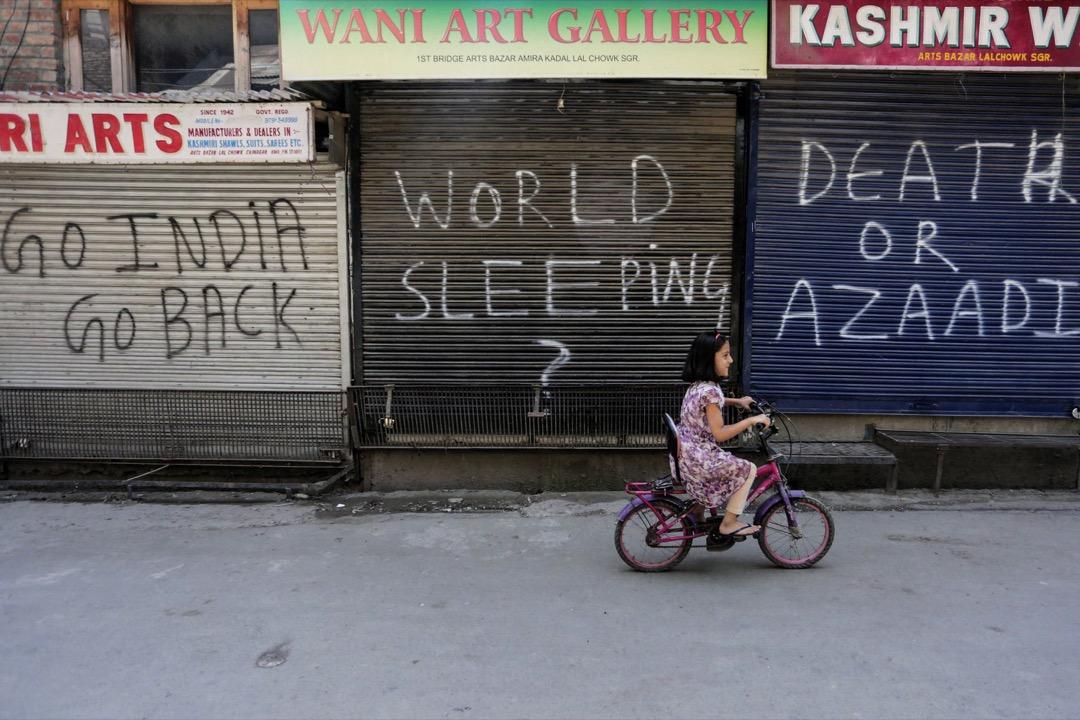 2017年8月11日,在印度斯里那加,一名克什米爾小女孩在關了門的商舖前踏單車。