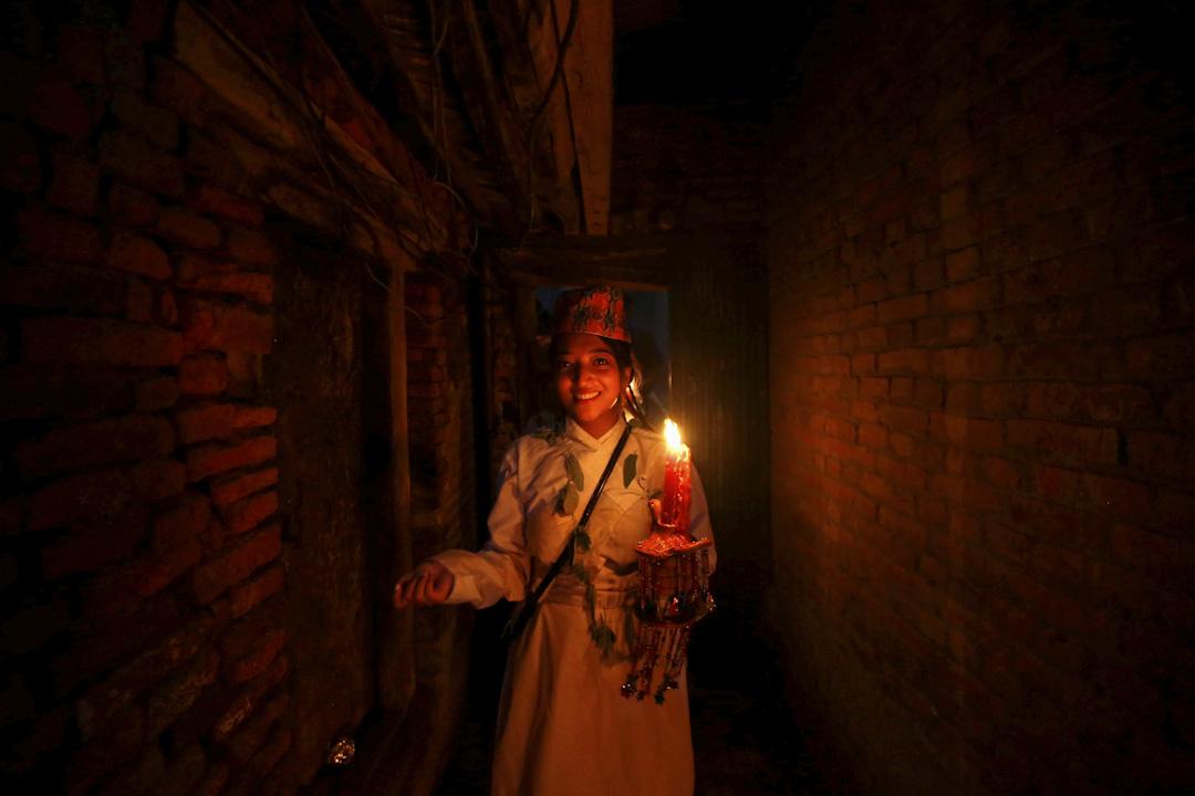 2017年8月9日,在尼泊爾勒利德布爾(又稱帕坦),正值當地的傳統節日光明節(Neku Jatra-Mataya Festival),一名信徒手持蠟燭走過巷道,笑容可掬。