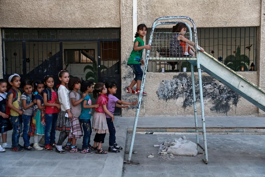 2017年8月16日,在敘利亞城鎮杜馬,一群學生在破舊的學校操場上嬉戲。